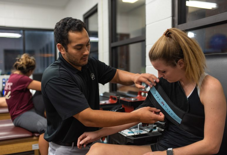 An athletic trainer working with a girl's shoulder