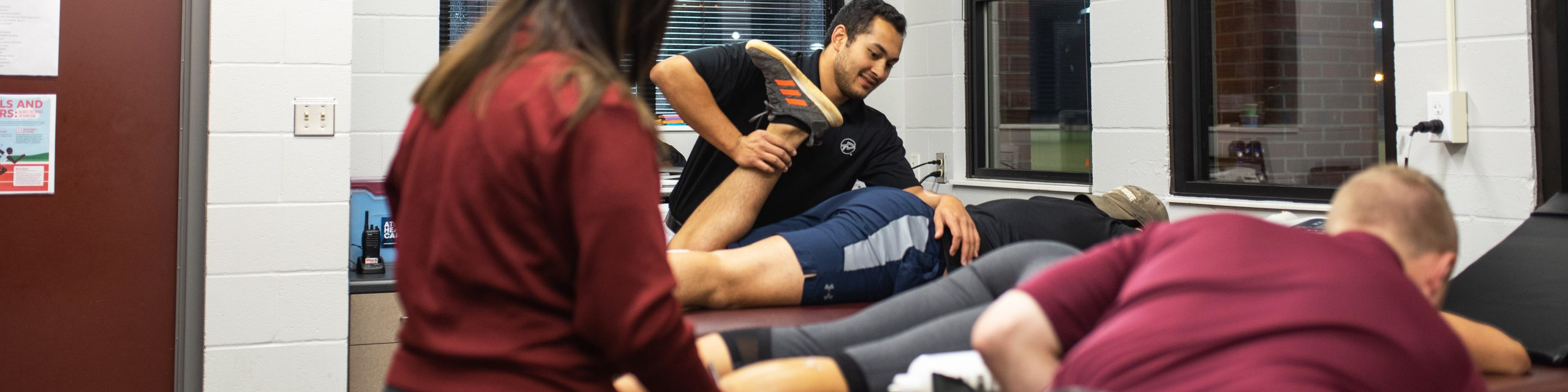 An athletic trainer helping a person with their leg