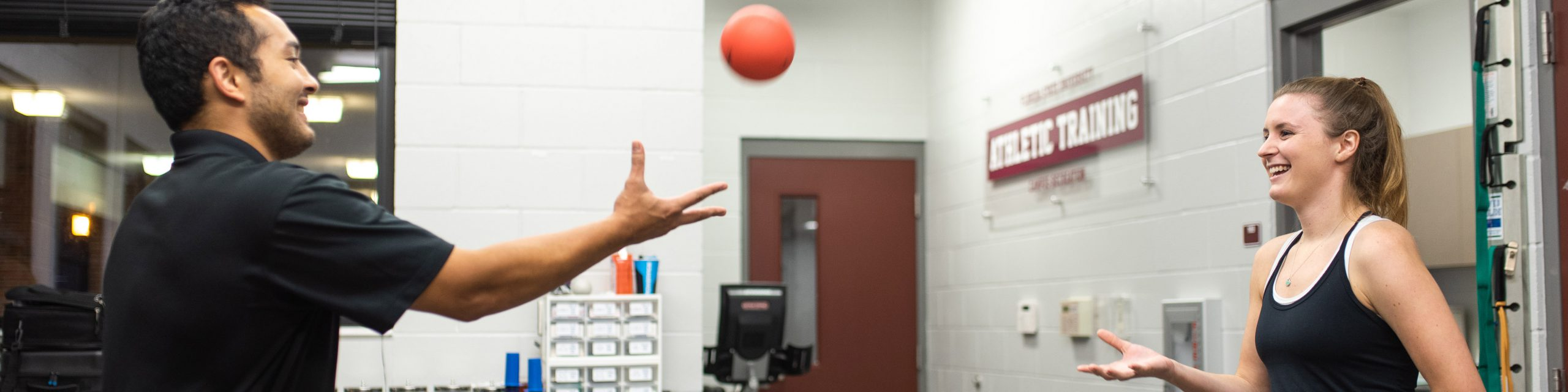 Athletic Trainer throwing a ball to a patient