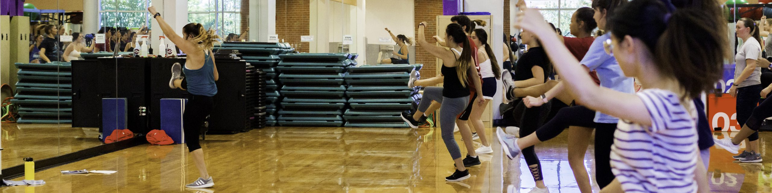 People participating in a group fitness dance class.