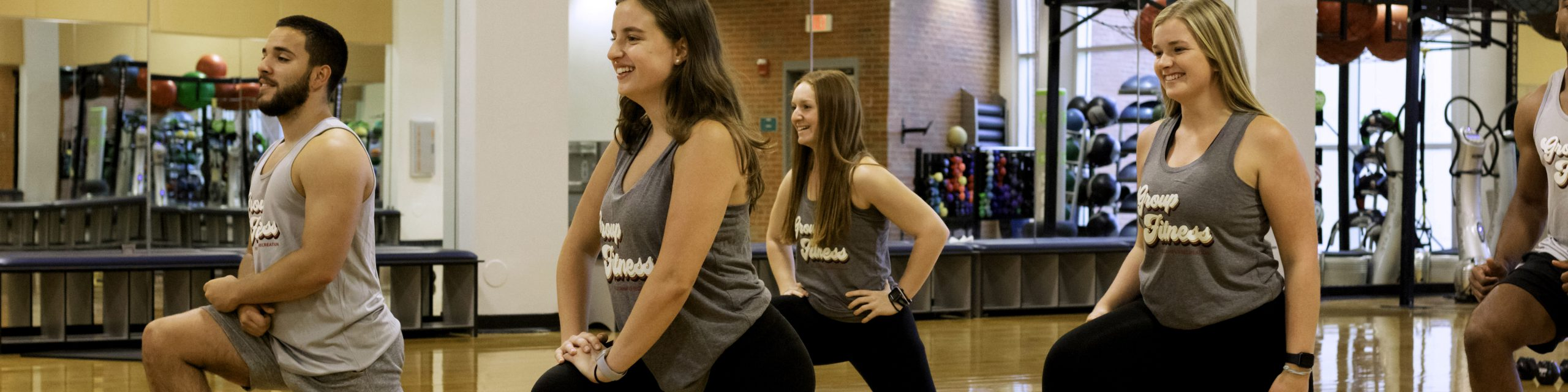 A group of people lunging in a group fitness class