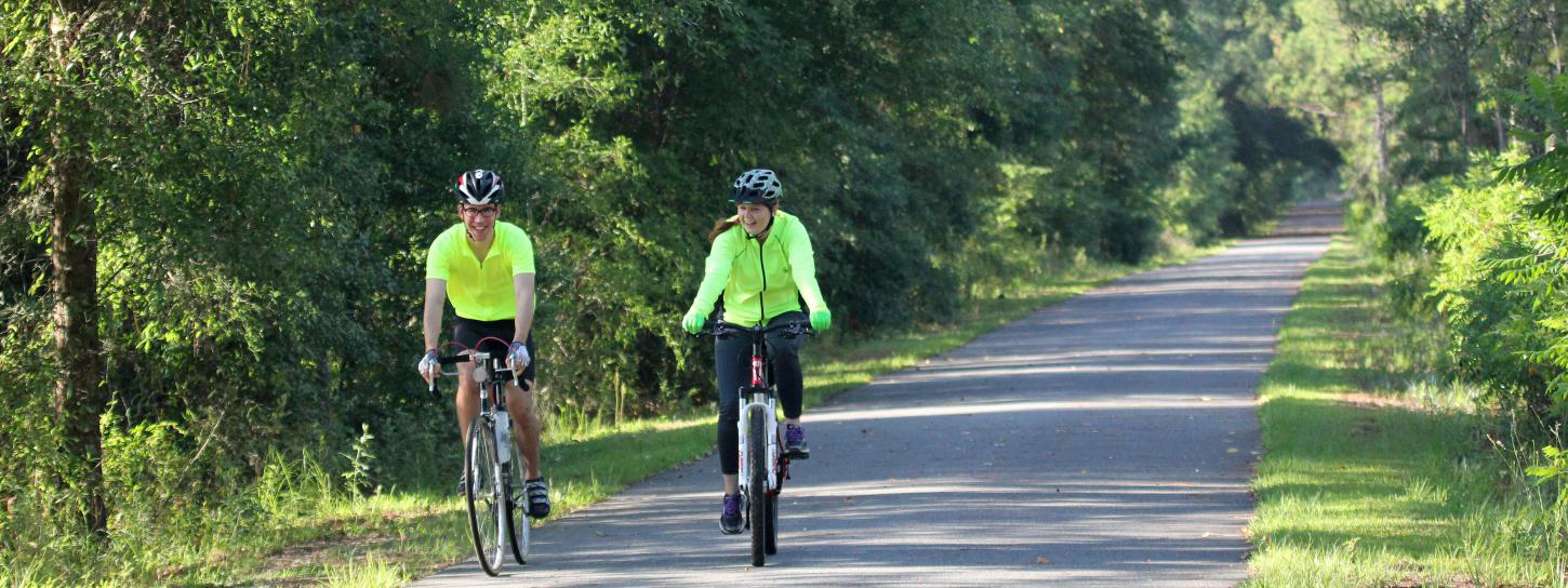 2 people bike riding on the St. Marks trail.