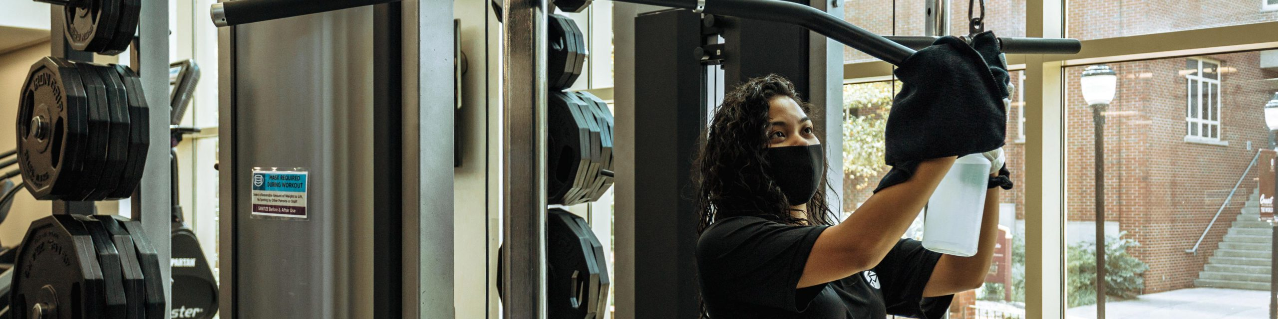 A girl wearing a facial covering cleaning equipment at the gym.