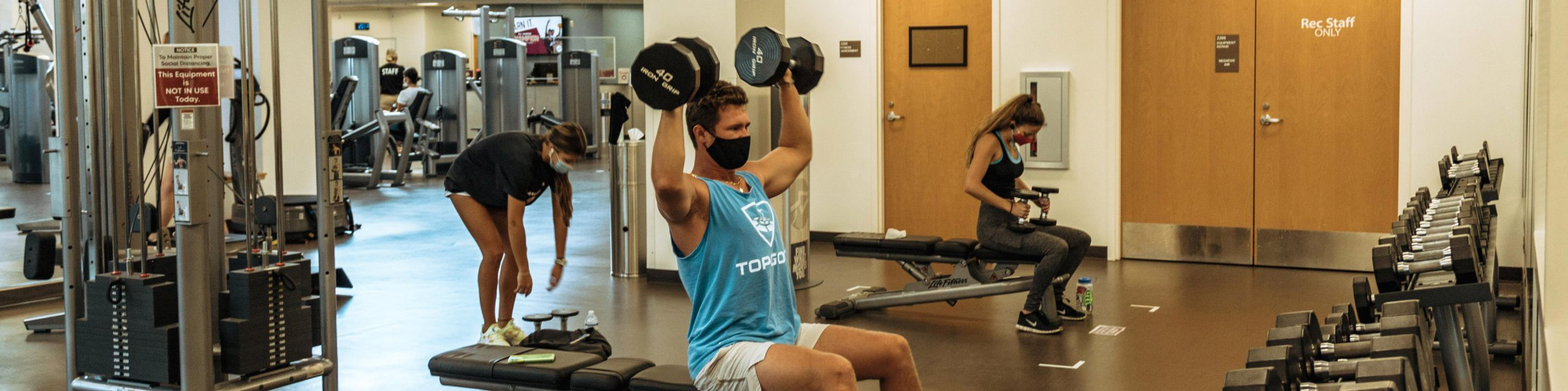A man wearing a mask lifting weights.
