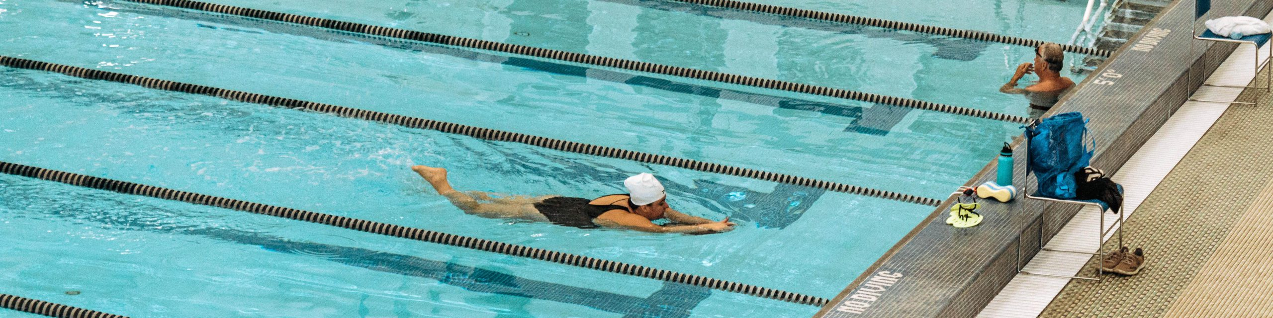 A women using a kick board in the Leach Pool.