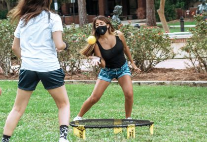 Group of masked people play spike-ball on Landis Green.
