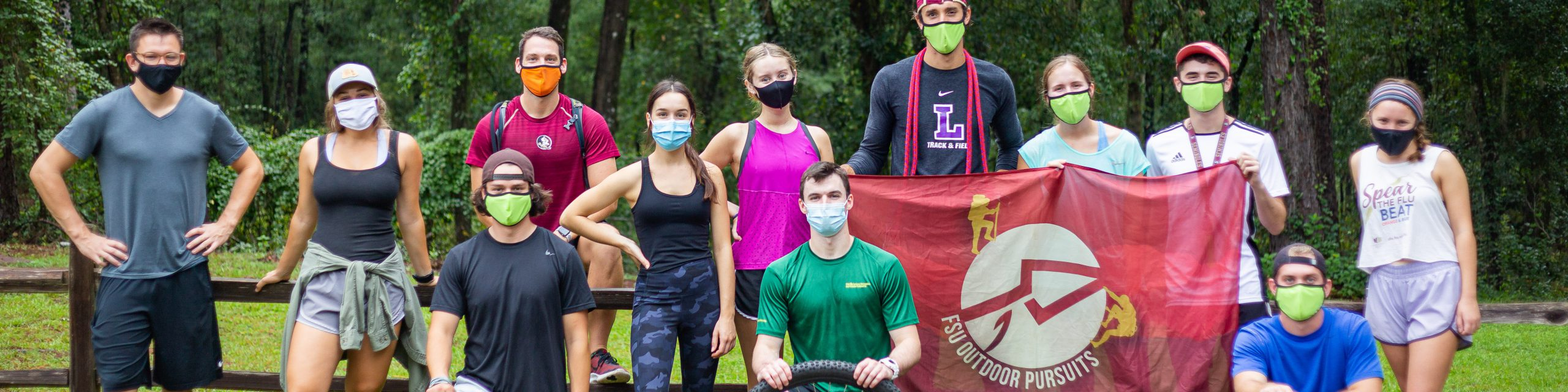 A group of masked people holding the outdoor pursuits banner.