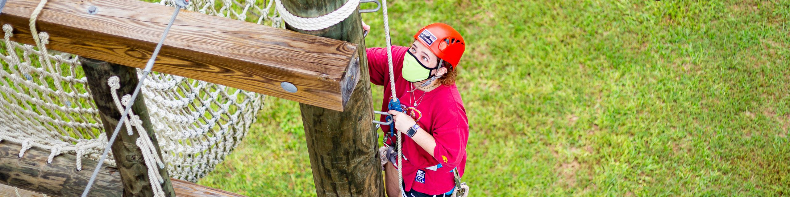 A girl wearing a facial covering climbs the challenge course at The Rez.