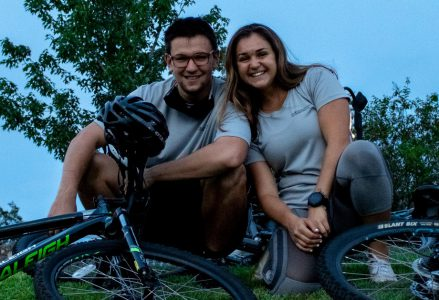 A girl and a guy squat by bikes.